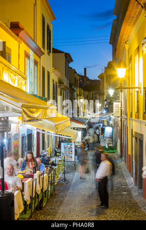 View of cafes in cobbled street in old town at dusk, Funchal, Madeira, Portugal, Europe - Stock Photo