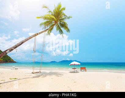 Beautiful tropical island beach with coconut palm trees and swing - Stock Photo