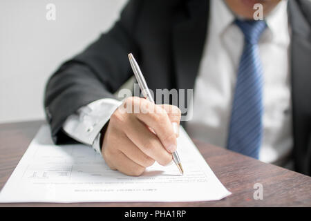 Businessman writing on application form and waiting for interview for get job in office - Stock Photo