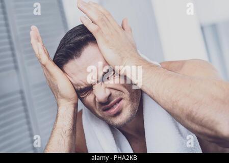 Suffering man feeling severe headache - Stock Photo