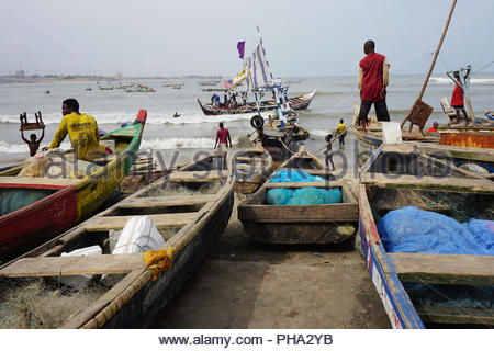 Wooden fisherboats coming from the fishing at the ocean into the port of Accra in Ghana - Stock Photo