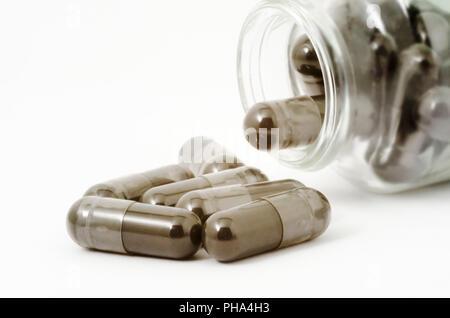 bottle of pills spilled on white background