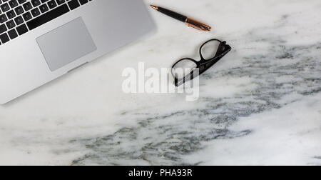 Marble desktop setting with laptop with pen and reading glasses - Stock Photo