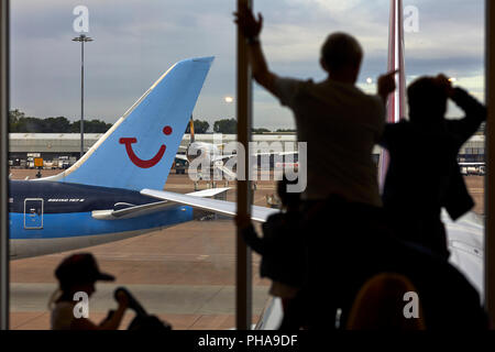 TUI Airways Boeing 787-8 Dreamliner at Manchester Airport as a family view the runway from inside  the terminal window - Stock Photo