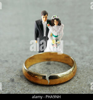 Married couple and broken gold wedding band - Stock Photo