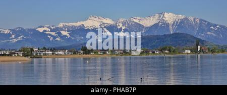 Shore of lake Zurichsee and snow capped mountain Grosser Speer - Stock Photo