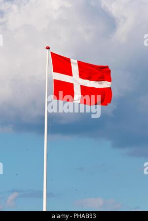 danebrog - flying danish flag - Stock Photo