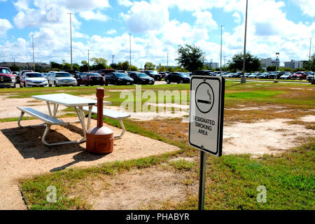 Designated Smoking Area sign outside with bench, cigarette disposal receptacle, and parking lot in background. - Stock Photo
