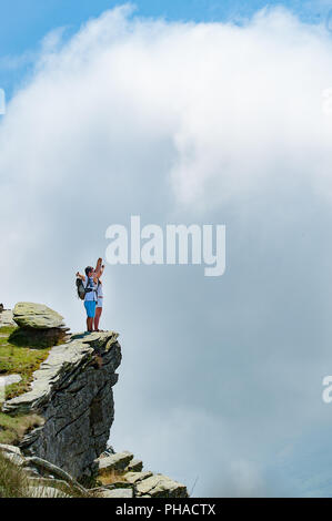 Travel concept: young tourists couple with backpacks standing on the top of a cliff with approaching puffy white cloud. Copy space. - Stock Photo