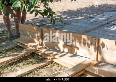 Man building a wooden fence. Workers pick up wooden boards for the fence formwork. Wooden formworks for concrete at construction site. - Stock Photo