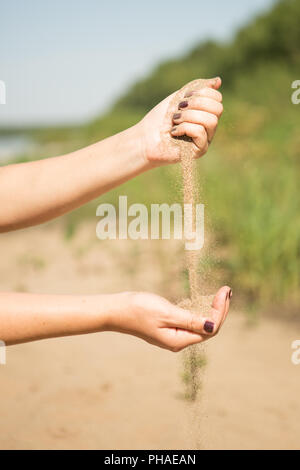 sand running through hands of woman in the beach - Stock Photo