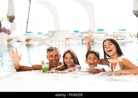Happy young family having fun inside a swimming pool outdoors in summer with cocktails, waving hands - Stock Photo