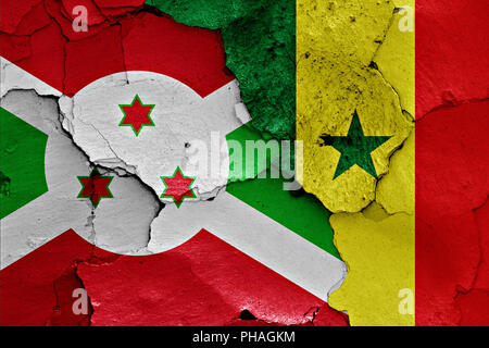 flags of Burundi and Senegal painted on cracked wall - Stock Photo