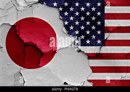 flags of Japan and USA painted on cracked wall - Stock Photo