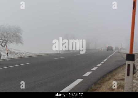 Cars drive in the fog on slippery road - Stock Photo