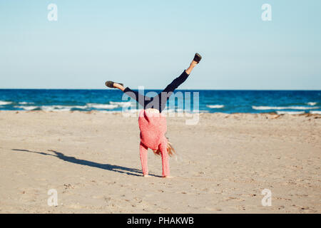 Portrait of funny white Caucasian child kid teenager, doing cartwheel playing on beach on sunset, autumn fall season, happy lifestyle childhood concep - Stock Photo