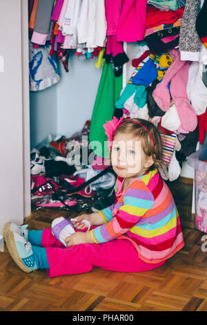 Portrait of cute adorable  little white Caucasian girl baby sitting on floor in wardrobe, wearing shoes, funny emotional face expression, lifestyle au - Stock Photo
