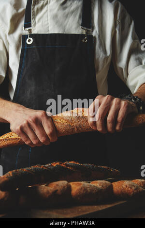 Hand breaks baguette - Stock Photo