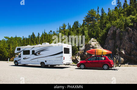 Road trip in RV with Red cars, kayaks on top and bikes at the back with forest in background - Summer getaway - Stock Photo