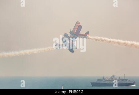 Bournemouth, UK. 31st August 2018. The Aero Superbatics Wingwalkers wing walkers perform at the 11th annual Bournemouth Air Festival - the Flying Circus. Astoria Cruise Ship in the sea below. Credit: Carolyn Jenkins/Alamy Live News - Stock Photo