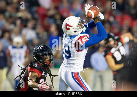 August 31, 2018: Montreal Alouettes slotback Adarius Bowman (19) misses a catch as Ottawa Redblacks Justin Howell (21) defends during the CFL game between Montreal Alouettes and Ottawa Redblacks at TD Place Stadium, in Ottawa, Canada. Daniel Lea/CSM. - Stock Photo
