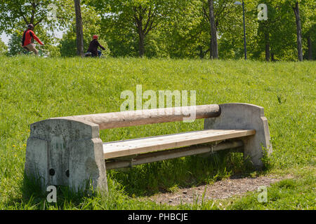 Massive wood-stone bench in a park invites to rest - Stock Photo
