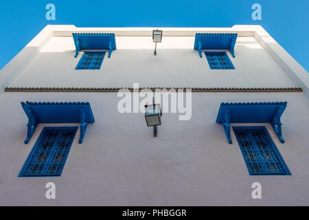 Beautiful ornamental blue windows on a white wall, Yasmine Hammamet, Tunisia - Stock Photo