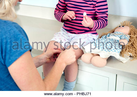 Mother putting bandage on daughter's knee - Stock Photo