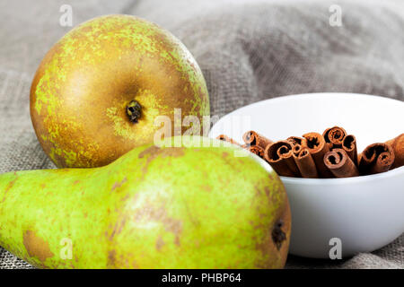 whole cinnamon sticks, lie in a white deep bowl next to green pears, on a linen tablecloth - Stock Photo