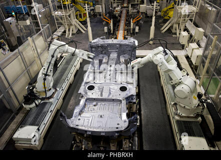 Robots work on a vehicle at Nissan Motor Co.s assembly plant in Tochigi, Japan on Thursday 12 Nov.  2009.  Photographer: Robert Gilhooly - Stock Photo