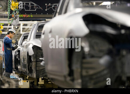 A worker works on a vehicle at Nissan Motor Co.s assembly plant in Tochigi, Japan on Thursday 12 Nov.  2009.   Photographer: Robert Gilhooly - Stock Photo