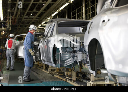 Workers work on a vehicle at Nissan Motor Co.s assembly plant in Tochigi, Japan on Thursday 12 Nov.  2009.  Photographer: Robert Gilhooly - Stock Photo