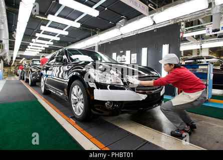 A worker makes final checks to a Nissan Motor Co., Fuga vehicle at the automaker's plant in Tochigi, Japan on Thursday 12 Nov.  2009.   Photographer:  - Stock Photo
