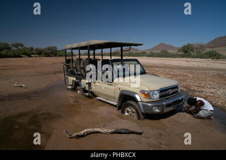Guide tries to jack up safari vehicle stuck in the sand of Hoarusib Riverbed, Puros, north of Sesfontein, Nambia, Africa - Stock Photo