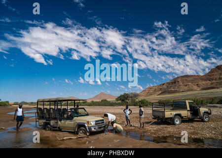 Rescuing safari vehicle stuck in sand of Hoarusib Riverbed, mountain range in background, Puros, north of Sesfontein, Namibia, Africa - Stock Photo