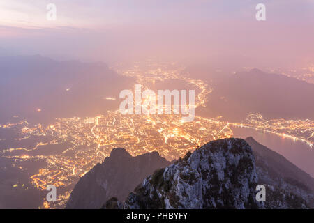 Illuminated city of Lecco seen from Monte Coltignone at dawn, Lombardy, Italy, Europe - Stock Photo