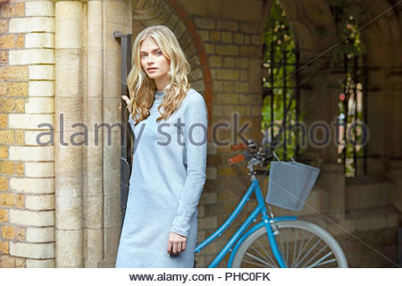 Young woman standing beside bicycle. - Stock Photo