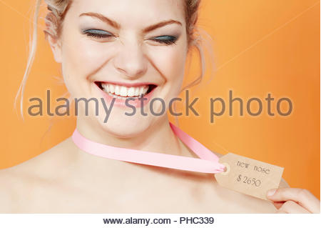 Young woman wearing price tag - Stock Photo