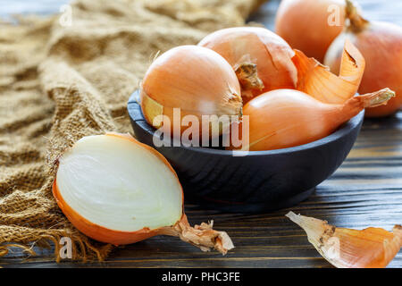 Fresh onion bulbs in a wooden bowl. - Stock Photo