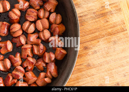 Partial overhead view of a frying pan with freshly cooked bite sized cocktail sausages over a bamboo board with copy space - Stock Photo