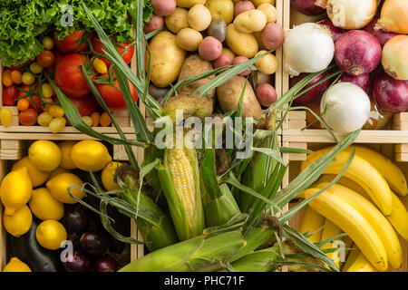 Fresh healthy assorted fruit and vegetables background displayed together in wooden boxes wooden table at an organic farmers market in a full frame cl - Stock Photo