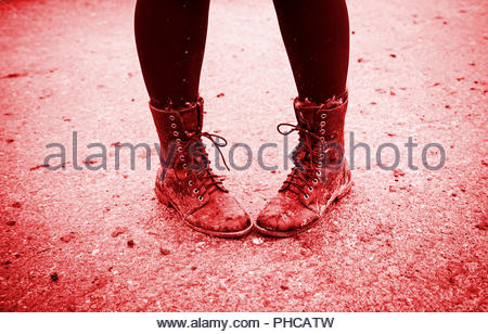 Women boots in the mud - Stock Photo