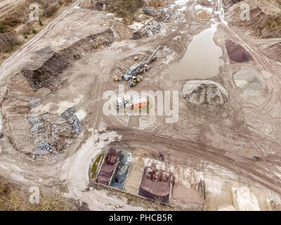 Aerial photo of a big sandy pit with machines - Stock Photo