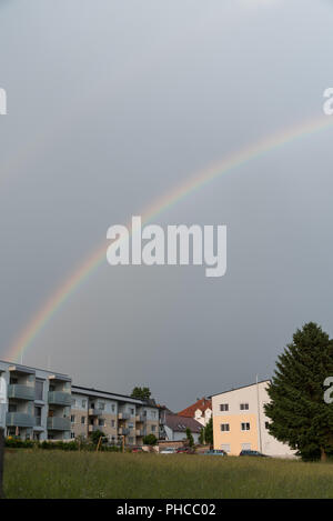Rainbow in bright colors in the rural area - Stock Photo