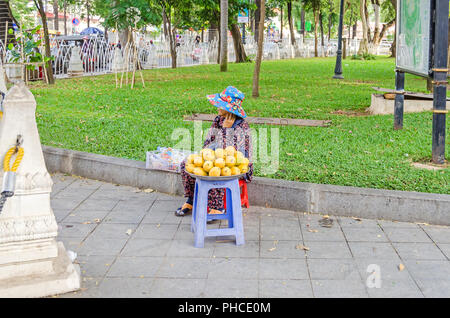 Phnom Penh, Cambodia - April 8, 2018: Woman with the typical Cambodian clothes  selling mangos in a garden of Wat Phnom (Mountain Pagoda) - Stock Photo