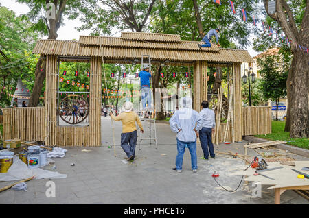 Phnom Penh, Cambodia - April 8, 2018: Workers  making a temporary gate out of bamboo stems  in a garden of Wat Phnom (Mountain Pagoda) - Stock Photo