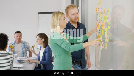 Two coworkers brainstorming on scheme - Stock Photo