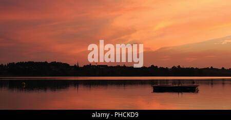 Bright orange sky over lake Pfaeffikon. Summer sunset in Switzerland. - Stock Photo