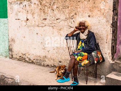 Elderly Cuban woman sits with her dog outside her humble home in poor section of Old Havana, Cuba. - Stock Photo