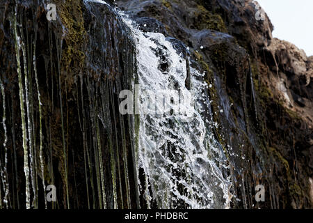 Detail of water flowing through a small waterfall. - Stock Photo